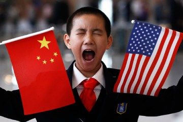 A boy who is waiting to greet U.S. Secretary of State Hillary Clinton at the National Museum makes a face while holding the U.S. and Chinese flags in Beijing May 4, 2012.  REUTERS/Shannon Stapleton (CHINA - Tags: POLITICS BUSINESS TPX IMAGES OF THE DAY)