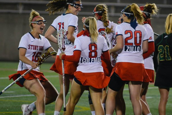 Players from Stony Brook's Women's Lacrosse team celebrate after freshamn Mackenzie Burns scores her first career goal as a Seawolf during Stony Brook's win over the Jacksonville Dolphins 16-6 on March 24th 2016. Credit: Joseph Ryder