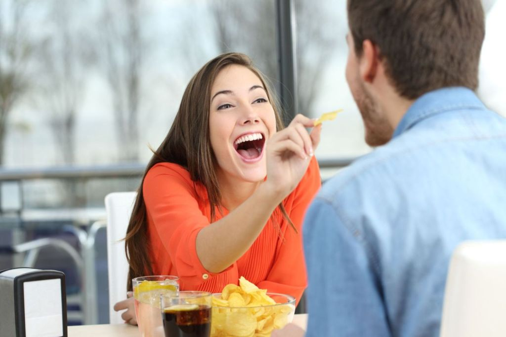 56102144 - playful couple eating chip potatoes and joking looking each other in a date in a coffee shop
