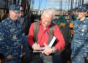 131018-N-SU274-047 CHARLESTOWN, Mass. (Oct. 18, 2013) Retired astronaut Buzz Aldrin autographs a photo for Cmdr. Sean Kearns, the 73rd commanding officer of USS Constitution, left, and Command Senior Chief Nancy Estrada during a tour of USS Constitution. Aldrin, the second person to walk on the  moon, was the lunar module pilot on the Apollo 11 moon landing mission on July 21, 1969. (U.S. Navy photo by Mass Communication Specialist 2nd Class Peter D. Melkus/Released)