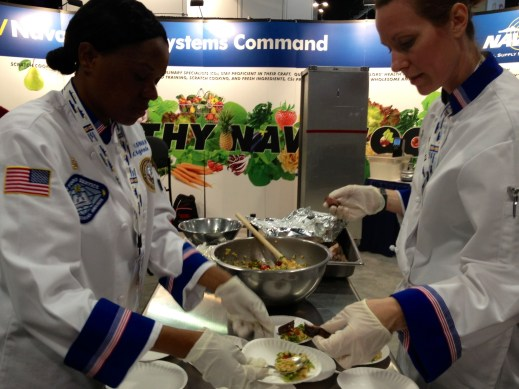 Chief Culinary Specialist (SW/AW) Nelle Kigembe and Culinary Specialist 1st Class (AW/NAC) Jamie Wyckoff plate a meal April 9 at NAVSUP's Sea Air Space booth. (Meghann Myers/STAFF)