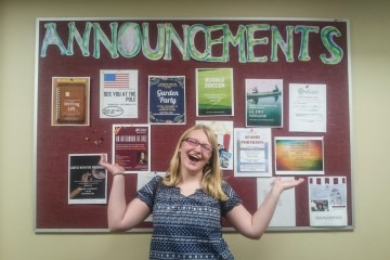 Student standing in front of Announcements board