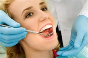 A young lady is having her regular checkup, dental exam. Beautiful smile.