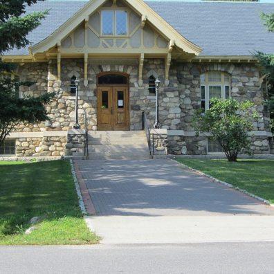 Stone building with brick walkway.