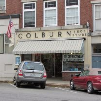 Tan awning with stripes adorns Colburn shoe store.