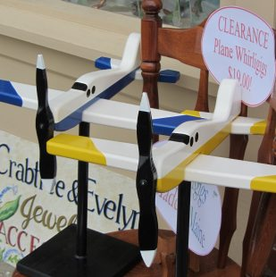 Blue and white, yellow and white whirligigs on the sidewalk sale.