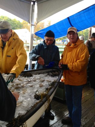 Volunteers helping out with the raw oysters on ice.