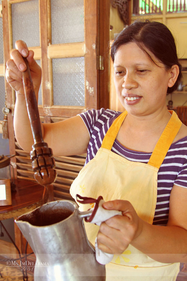 Here's Ate Baby who patiently stirred our hot, rich, sweet and thick tsokolate on a heavy cast-iron chocolatera (tsokolatera) with a batidor or batirol that is made from guava tree trunk.