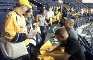 Defenseman Kevin Klein signs a jersey for a fan.