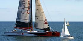 """Größenverhältnis des 37,80 Meter langen Katamarans """"Orange II"""" gegenüber einer Segelyacht. © Martin-Raget"""