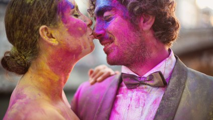 Bride and groom in the city playing with holi powder