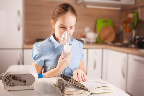 Girl doing inhalation and reading book