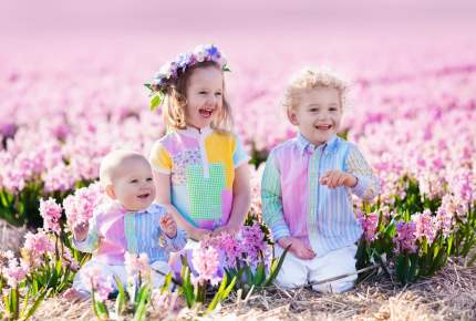 Three children playing in beautiful hyacinth flower field.