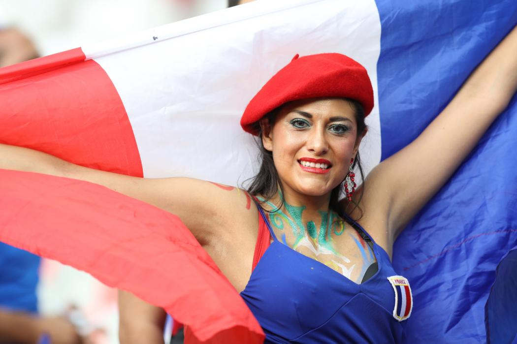 A France fan wearing a red beret holds up a French flag ahead of the Euro 2016 final football match between Portugal and France at the Stade de France in Saint-Denis, north of Paris, on July 10, 2016. / AFP PHOTO / Valery HACHE