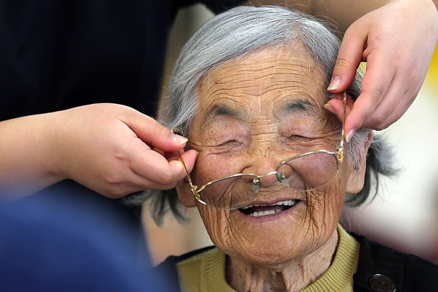 """Ayako Wakasu, 94, smiles as her glasses are adjusted by a staff member at a day care facility on Gogo Island in Matsuyama, Ehime Prefecture, Japan, on March 22, 2013."""