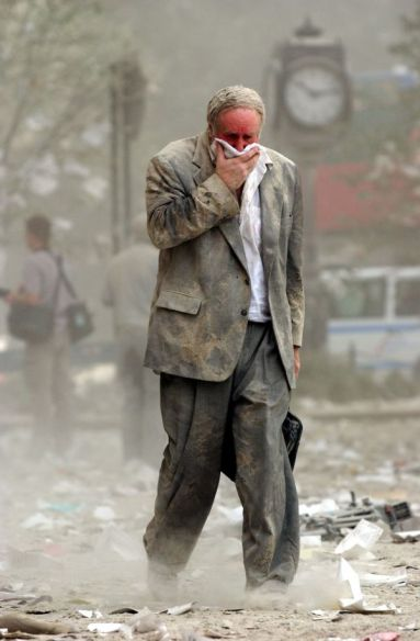 (FILES) This file photo taken on September 11, 2001 shows Edward Fine covering his mouth as he walks through the debris after the collapse of one of the World Trade Center Towers in New York. The Twin Towers of the World Trade Center which were struck by hijacked airplanes collapsed on that day, claiming 2,753 lives. September 11, 2016 marks the fifteenth anniversary of the event. / AFP / STAN HONDA