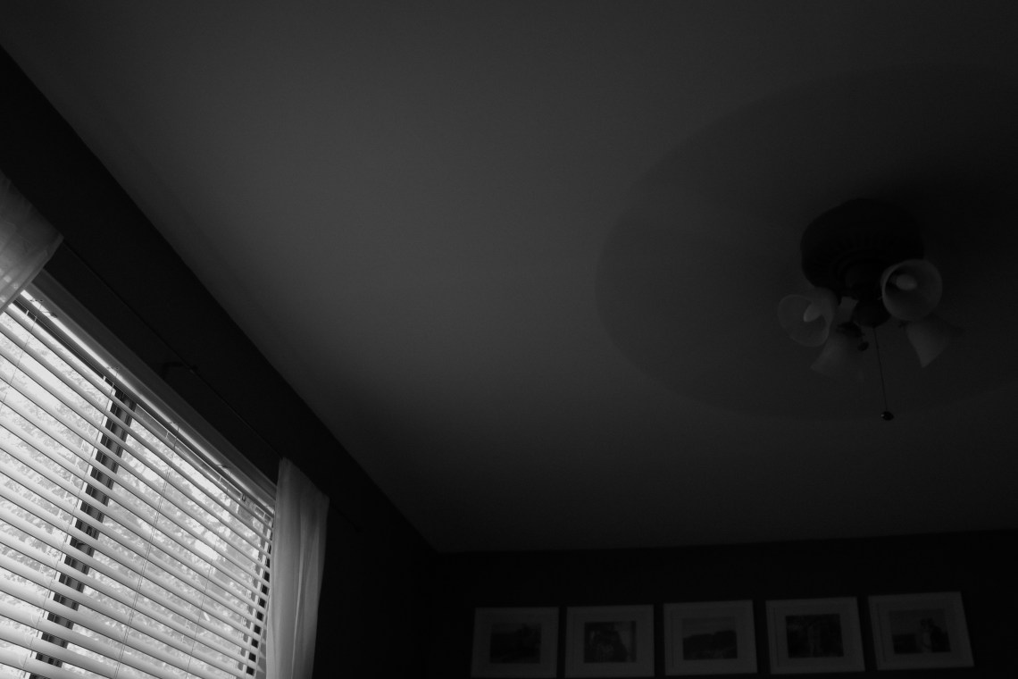 Black and white photo of a bedroom ceiling fan with window in left corner