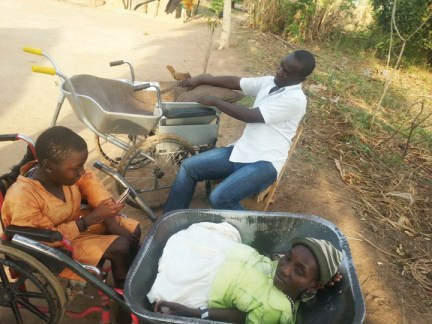 Eunice Atim in wheelbarrow as new wheelchair readied