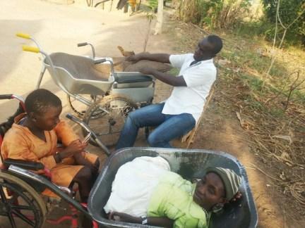 Eunice Atim in wheelbarrow as new wheelchair readied