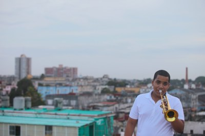 "They call him ""El Niño Jesus."" He is the next generation of Cuban jazz trumpet. In the film ""Tengo Talento,"" his mentor Julio Padrón, a world renowned trumpeter, introduces us to this young man who is only 15 years old with a spectacular sound that promises to make him a big star. In this photo, Jesus is practicing on the rooftop of his apartment in Vedado, Cuba, with downtown Havana in the background. – Photo: Eli Jacobs-Fantauzzi"