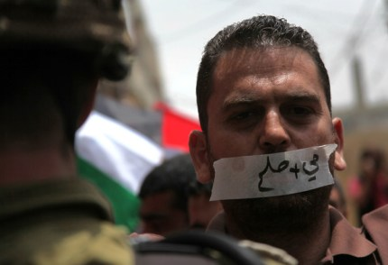 "A protester wears tape on his mouth reading ""water and salt"" during a rally in solidarity with hunger striking prisoners at al-Aroub refugee camp near the occupied West Bank city of Hebron. – Photo: Mamoun Wazwaz, APA"