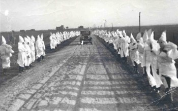 "Ku Klux Klan membership grew after the destruction of Black Wall Street. Here they gather in Drumright, Okla., in 1922, the following year. And in 2001, 80 years later, when the Tulsa Race Riot Commission recommended in a 178-page report that survivors be paid reparations, calling it a ""moral obligation,"" hate calls flooded into the Greenwood Cultural Center, where a plaque lists the financial claims of the over 200 who've sued, adding up to $2,719,745.61. – Photo: Tulsa Historical Society"
