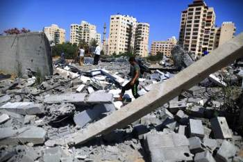 A Palestinian boy inspects the damage following overnight Israeli airstrikes in Gaza City. – Photo: Mohammed Omer