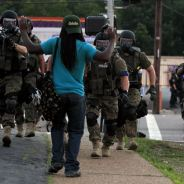 Michael Brown murder aftermath white cops in riot gear aim gun at Black man hands raised Ferguson Mo 081114 by AP-VOA