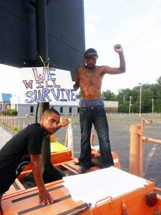 On West Florissant, two young protesters, unintimidated by a mobile highway sign, declare their determination to survive police terrorism and fight for freedom. – Photo: JR Valrey, Block Report