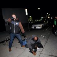A white undercover police officer, his hand and gun shaking after being spotted and identified as a cop posing as a protester, points his gun at the photographer as his partner wrestles the protester who outed them to the ground and arrests him. The white cop, suspicious for his out-of-date clothes, acted scared and confused, losing the scarf that had masked his face and handling his gun with cowboy bravado to conceal his fear. – Photo: Noah Berger