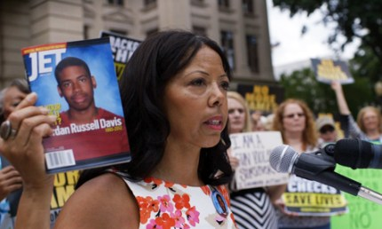 Lucia McBath, the mother of Jordan Davis, holds a copy of Jet Magazine with her son, Jordan Davis, on the cover as she speaks at a rally seeking justice.