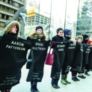 """Called """"Chicago shows love to Jon Burge torture victims,"""" supporters staged a dramatic demonstration in the snow on Feb. 14, 2015, as Chicago deliberated reparations. The long line named 118 victims, including Aaron Patterson. – Photo: Sarah Jane Rhee"""