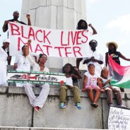 "Protest at Robert E. Lee Circle. Lee was the commander in chief of the Confederate States of America. People wore ""Resurrect the Village: Unity Equals Power"" t-shirts. The chant was, ""Take down Robert E. Lee and all symbols of white supremacy!"" – Photo: Wanda Sabir"
