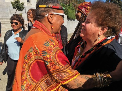 In another reunion of old friends, Mama C, Charlotte O'Neal, who, with her husband Pete, live in exile in Tanzania, still serving the people, greets Shukuru Sanders. – Photo: Malaika Kambon