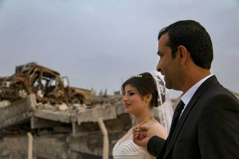 A groom holds his bride's hand while walking past damaged buildings and vehicles as they head to their wedding ceremony in the northern Syrian town of Kobani, October 23, 2015. This Kurdish couple is the first to have a civil marriage after the town was captured from Islamic State by Kurdish-led forces and it was declared part of the system of autonomous self government established by the Kurds. Picture taken October 23, 2015. REUTERS/Rodi Said EDITORIAL USE ONLY. NO RESALES. NO ARCHIVE
