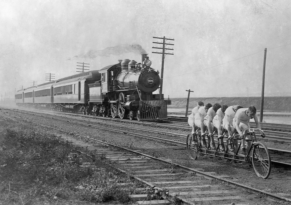 ca. 1896 --- Men calling themselves the Stearns Sextuplets race a six-man bicycle against the Empire State Express, a steam locomotive pulling four cars. --- Image by © CORBIS