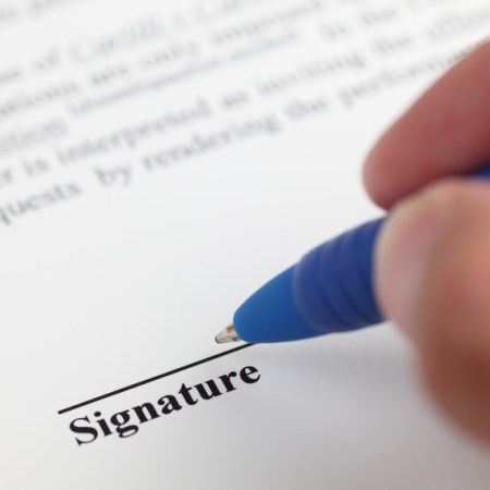 Businessman signing contract. Focus on the end of ballpoint pen. Shallow depth of field. Close-up.