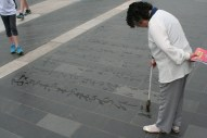 At the entrance to the Temple of Heaven, this woman was doing calligraphy with an oversized brush dipped in water. You can see the other characters that have started to evaporate. Very zen.