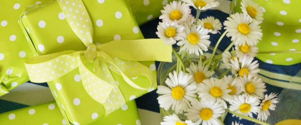 A small bouquet of daisies surrounded by presents wrapped in spring-green paper with white polka-dots