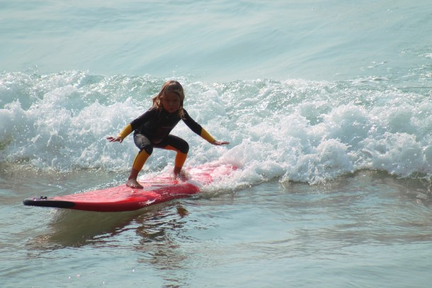 Child riding a wave on a surfboard