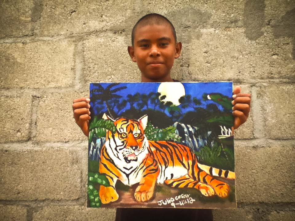 Julio Cesar holding up tiger painting