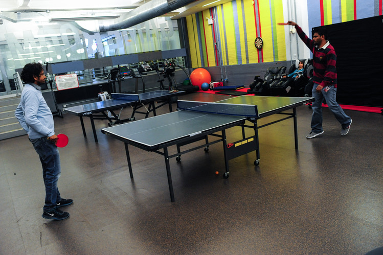 Google staff members play ping pong at Google's offices in New York in 2013.