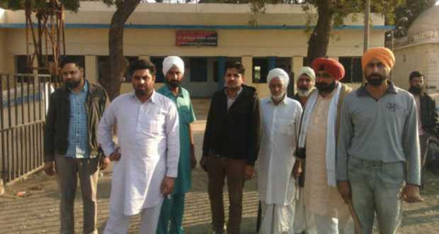 The Punjabi farmers who were attacked stand outside a police station in Bhuj, Gujarat.