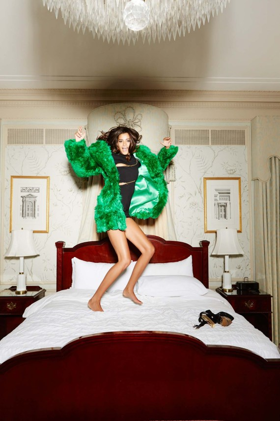 Woman jumping on the bed in a big furry green coat