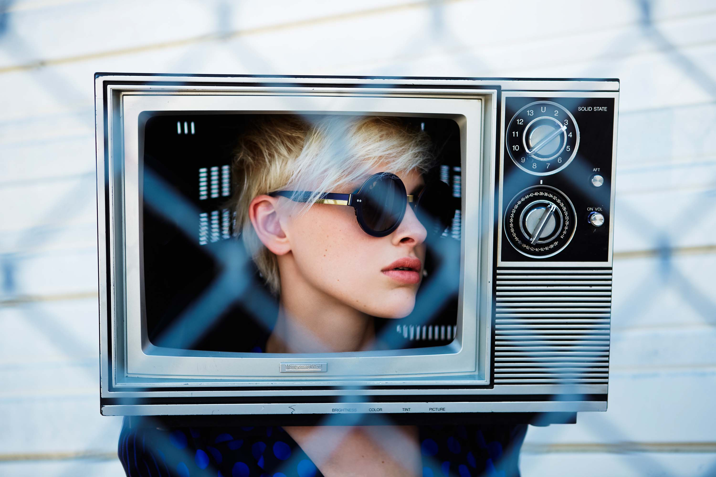 Woman with Round Sunglasses on with TV on her Head