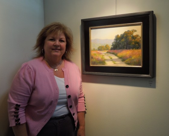 Linda Mutti stands beside one of her paintings at Studios on the Park