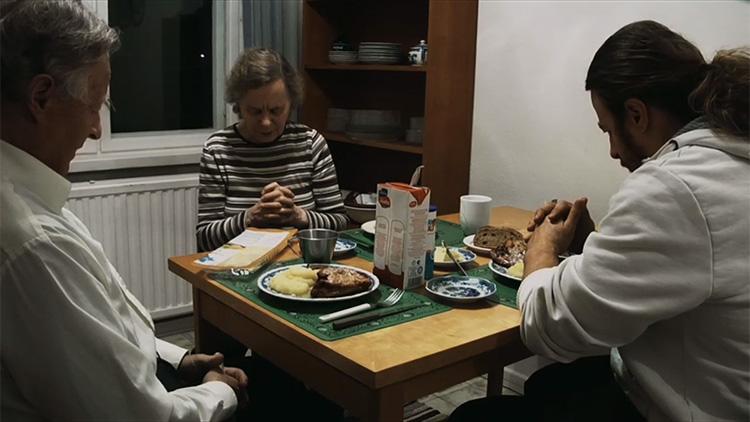 Michael (oik.) rukoilee isänsä ja äitinsä kanssa ennen ateriaa.