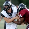 Junior Kyle Ball pushes away from Lawrence High defensive lineman. Ball had 12 tackles against Lawrence High. Photo by Marisa Walton