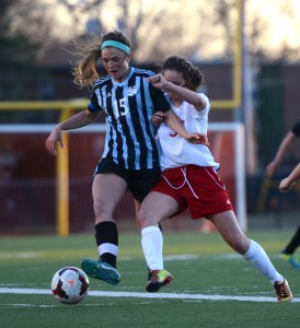 Junior Emma Braasch fights for ball against opponent. By Katie Lamar