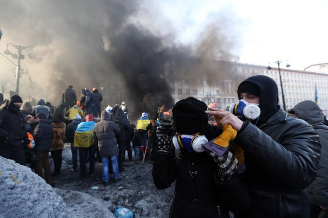 A protester puts a gas mask on a young woman behind a barricade on Grushevsky Street in downtown Kiev during clashes with riot police on Saturday, Jan. 25, 2014.